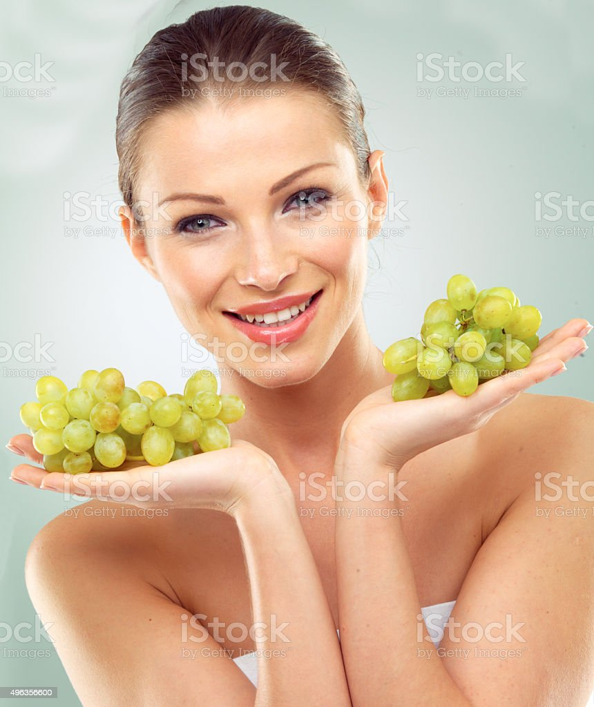 Young Woman Holding A Bunch Of Green Grapes Stock Photo More Pictures Of 2015