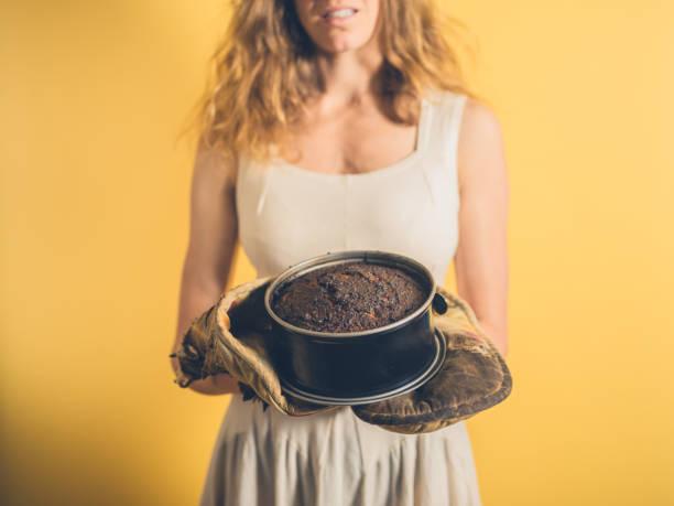 young woman holding a burnt cake - burned cooking imagens e fotografias de stock