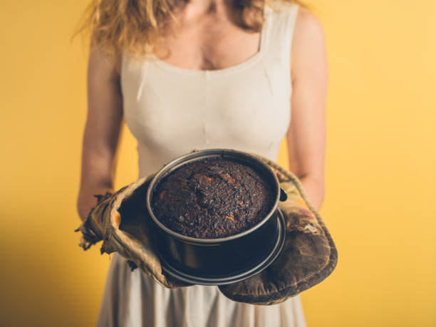 Young woman holding a burnt cake stock photo