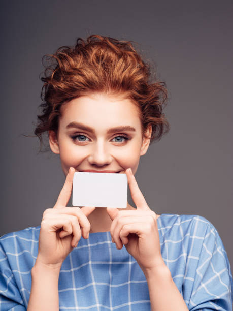 Young woman holding a business card stock photo