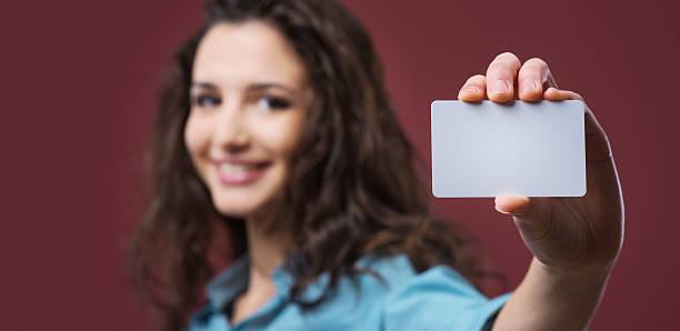 young woman holding a business card - identity card stock photos and pictures