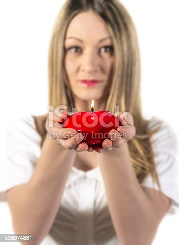 94172415 istock photo Young woman holding a candle heart 536974881
