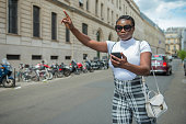 istock Young  woman holding a Cellphone waiting for a Uber taxi 1254573246