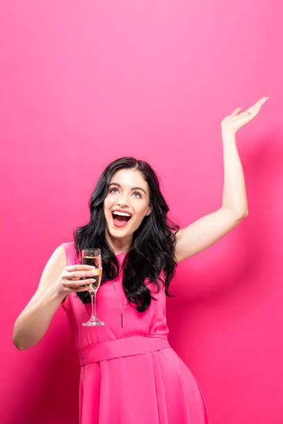 joven mujer sosteniendo una flauta de champagne - sólido fotografías e imágenes de stock