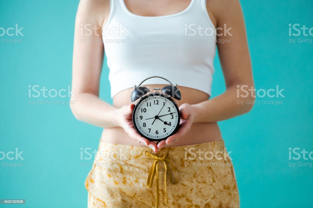 Young woman holding a clock over blue background. stock photo
