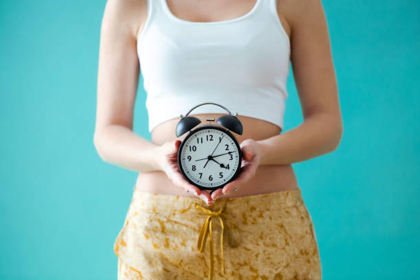 Young woman holding a clock over blue background. Close-up of a young woman holding a clock over blue background. styles stock pictures, royalty-free photos & images