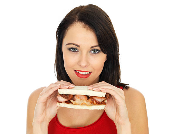 Young Woman Holding a Delicious Fresh Crispy Bacon Sandwich stock photo