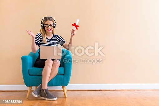 istock Young woman holding a diploma and her laptop 1082883294