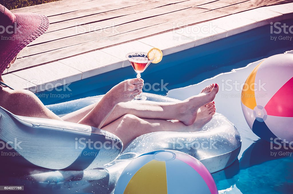 Young woman holding a glass of martini in swimming pool stock photo