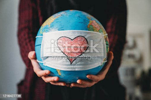 Young woman holding a globe with a face mask on it - Conceptual Coronavirus Covid-19 virus pandemic - Heart shape is drawn on the mask.
