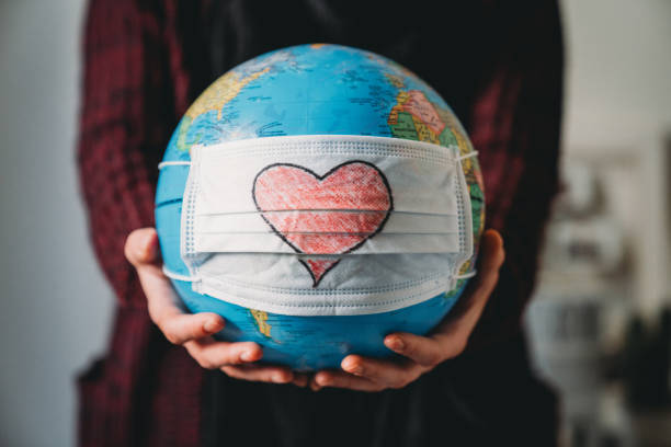 Young woman holding a globe with a face mask on it - Heart shape is drawn on the mask stock photo