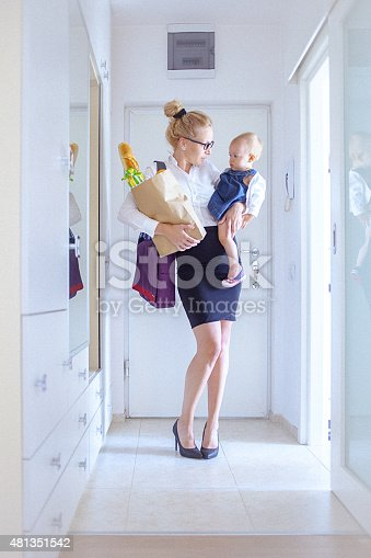 Attractive young mother in the entrance of her apartment, holds a grocery bag in one hand and her baby girl in another. The woman is dressed in white shirt and black skirt and wears a black eyeglasses and a briefcase. Her blonde hair is swept back from her face. Both, woman and a baby girl, looks happy. The woman could be a single mom coming back from the office. Shallow DOF; Soft focused; developed from RAW; retouched with special care and attention; small amount of grain added for best final impression; ready made for print and web use.