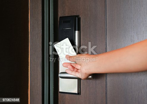 istock young woman holding a key card to unlock door. 970624548