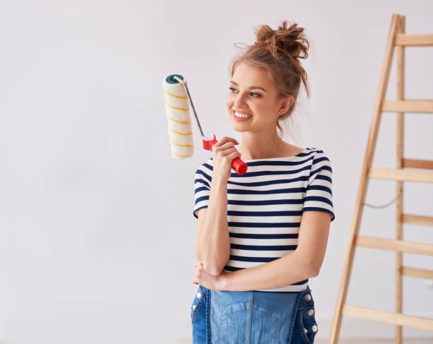Mujer joven sosteniendo un rodillo de pintura - foto de stock