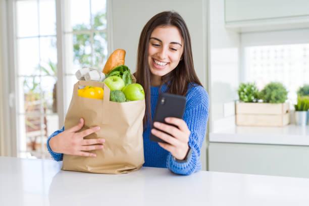 young woman holding a paper bag full of fresh groceries and using smartphone app for supermarket delivery - food delivery стоковые фото и изображения