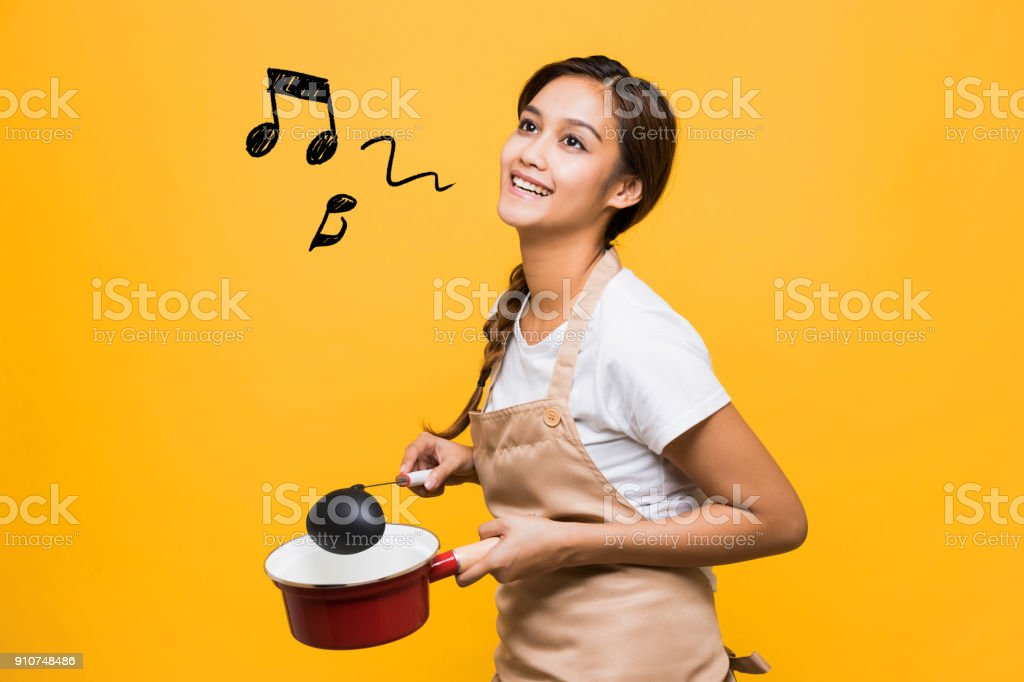 Young woman holding a pot and a ladle. stock photo