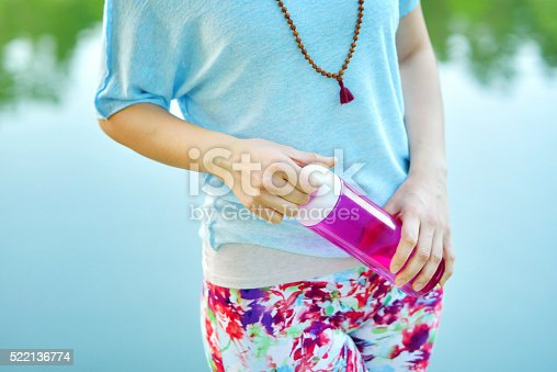 Young woman standing in the nature and holding a reusable water bottle in her hands.
