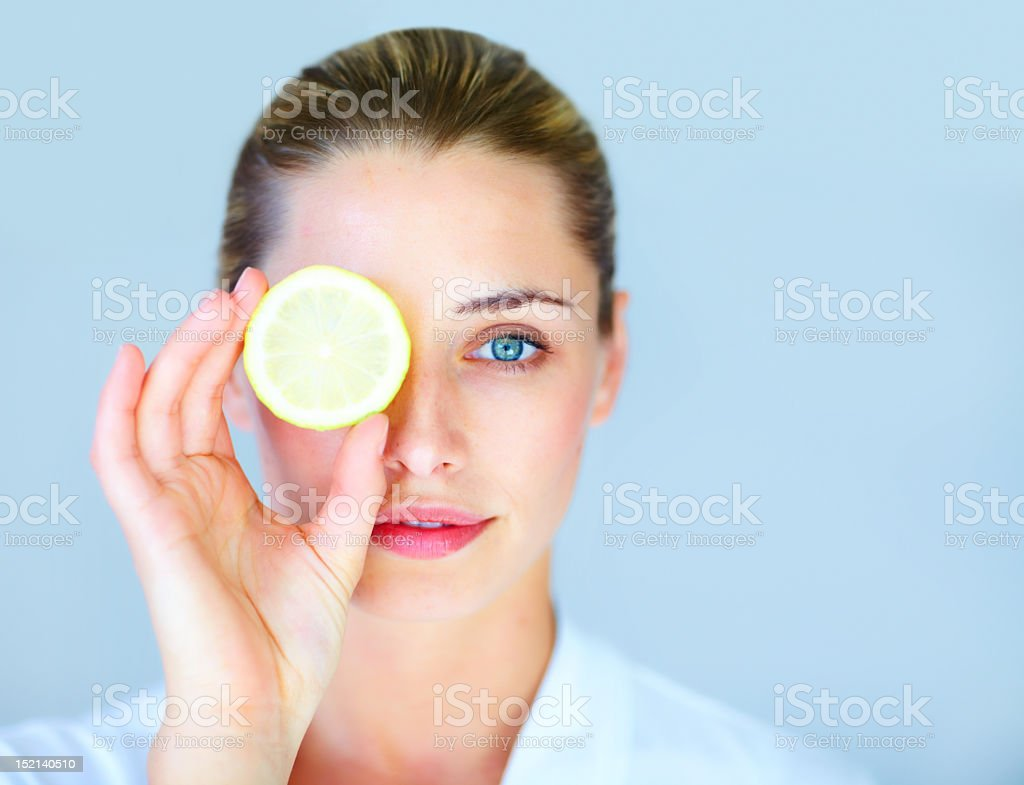 Young woman holding a slice of lemon in front of her eye royalty-free stock photo