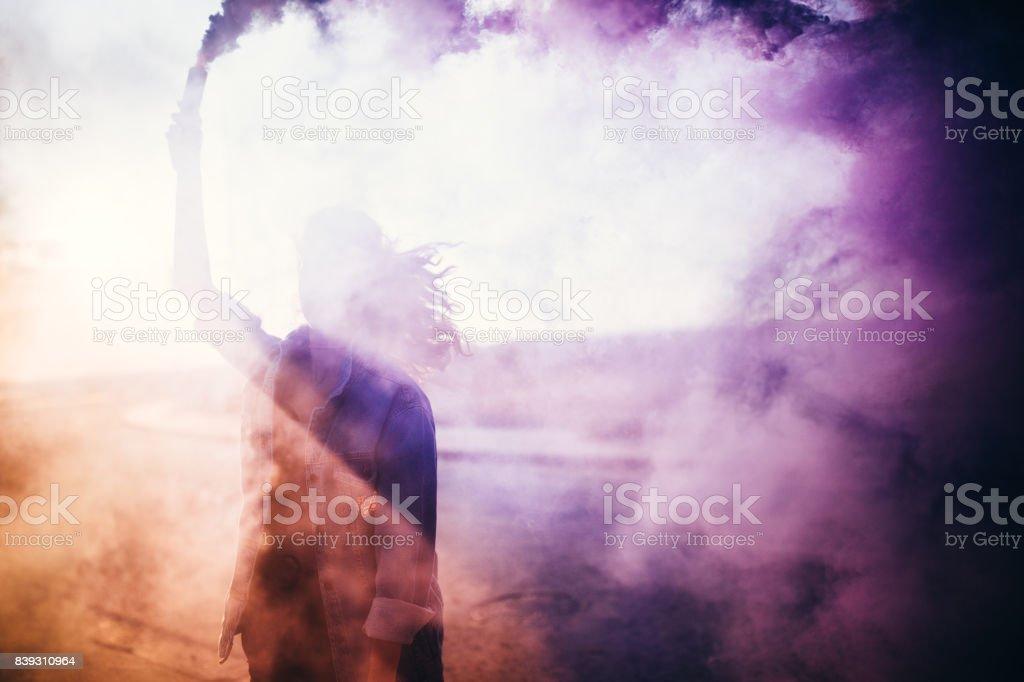 Mujer joven con una bomba de humo en las calles - foto de stock