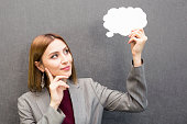 istock Young woman holding a speech bubble on a grey background 1063904798