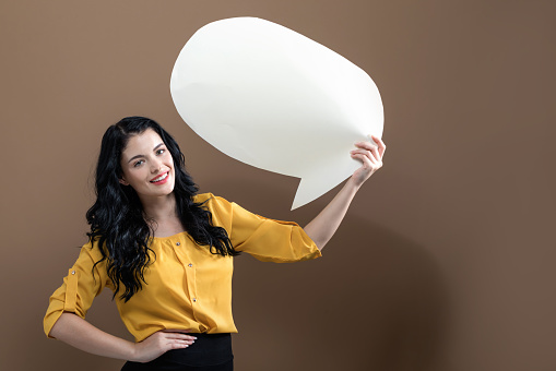 Young woman holding a speech bubble
