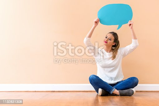 Young woman holding a speech bubble against a big interior wall