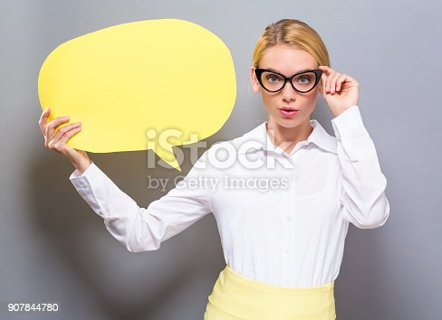 istock Young woman holding a speech bubble 907844780