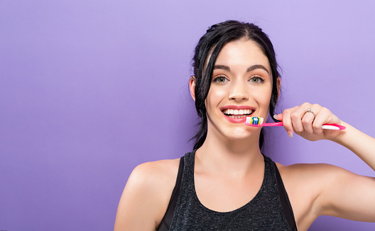 Young Woman Holding A Toothbrush Stock Photo - Download Image Now