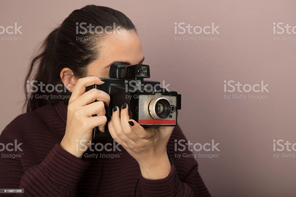 Jovem mulher segurando uma câmera vintage - foto de acervo