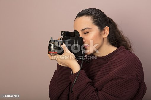 Female photographer taking a photo with a vintage camera she focuses on her subject in a side view