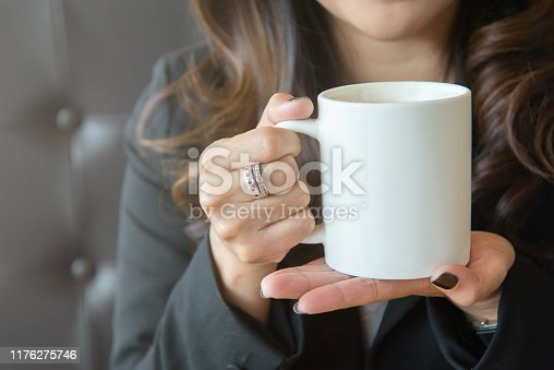 Young woman holding a white coffee cup with two hands outdoors and indoors.