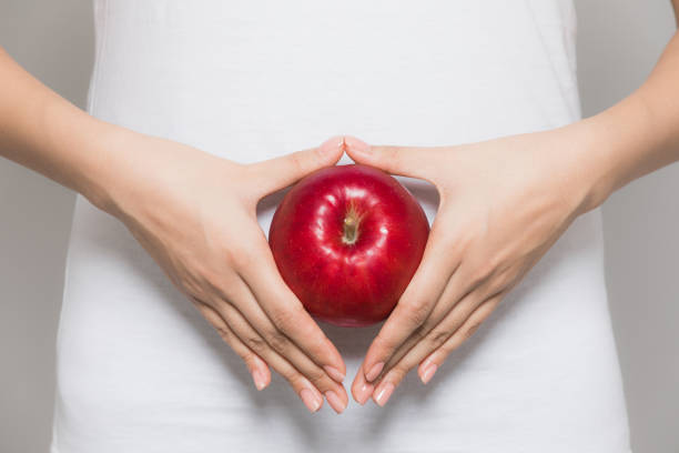 young woman holding an apple on her stomach. - dieta macrobiotica foto e immagini stock