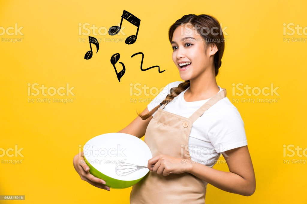 Young woman holding an eggbeater. stock photo