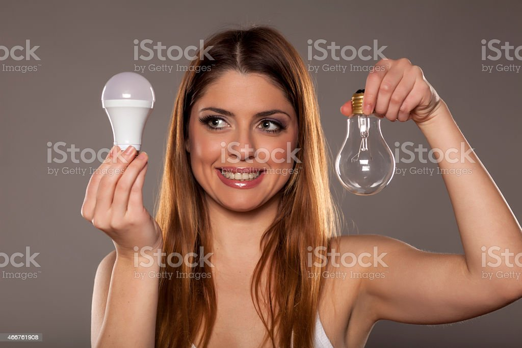 Young woman holding an old tungsten and new LED bulbs stock photo
