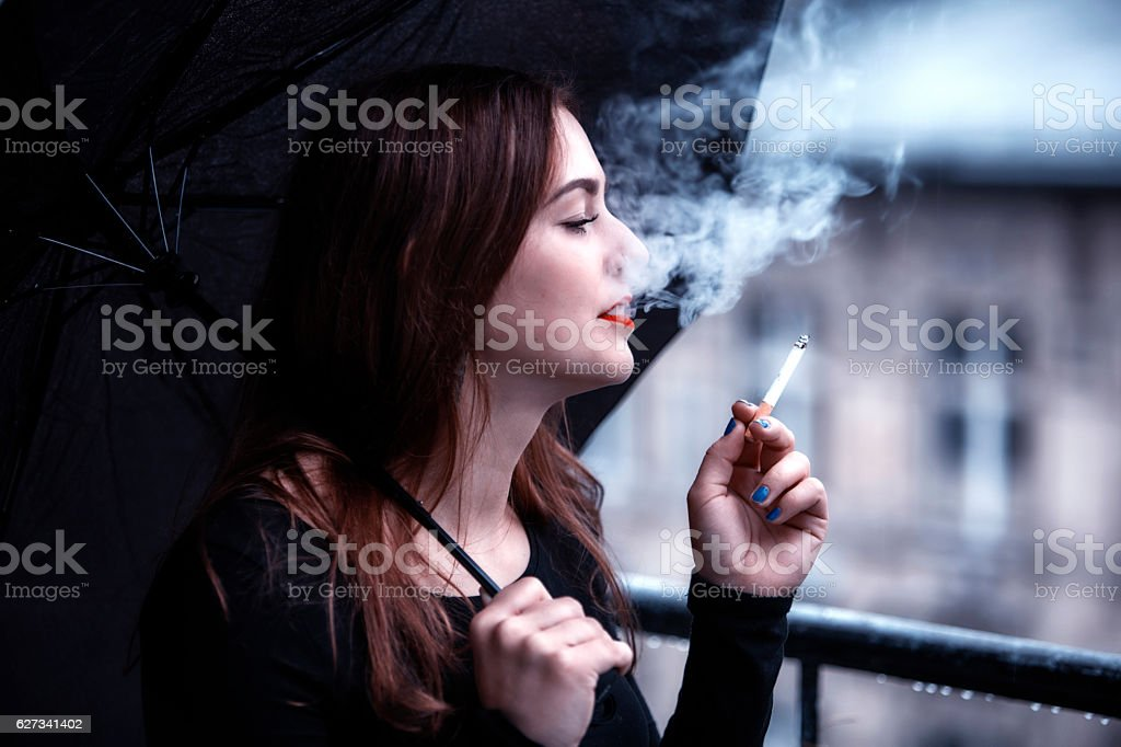 young woman holding an umbrella and smoking a cigarette stock photo