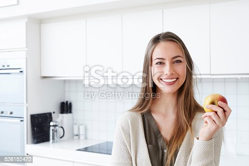 Young woman holding apple in kitchen, portrait