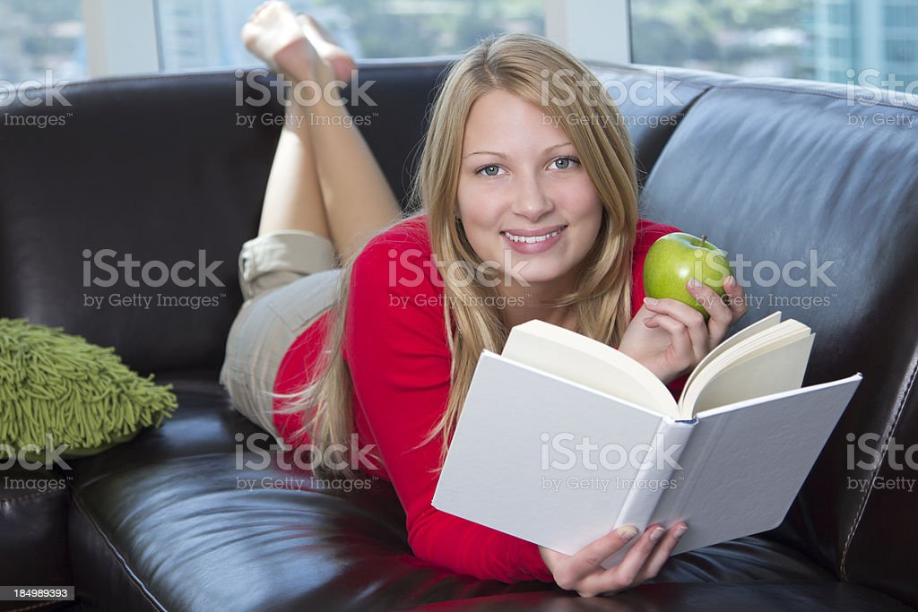 Young woman holding apple while reading book royalty-free stock photo