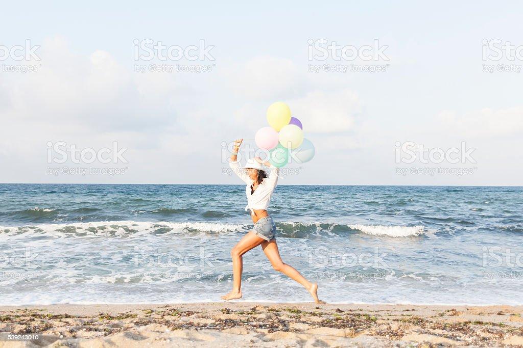 Joven mujer sosteniendo globos y corriendo en la playa foto de stock libre de derechos
