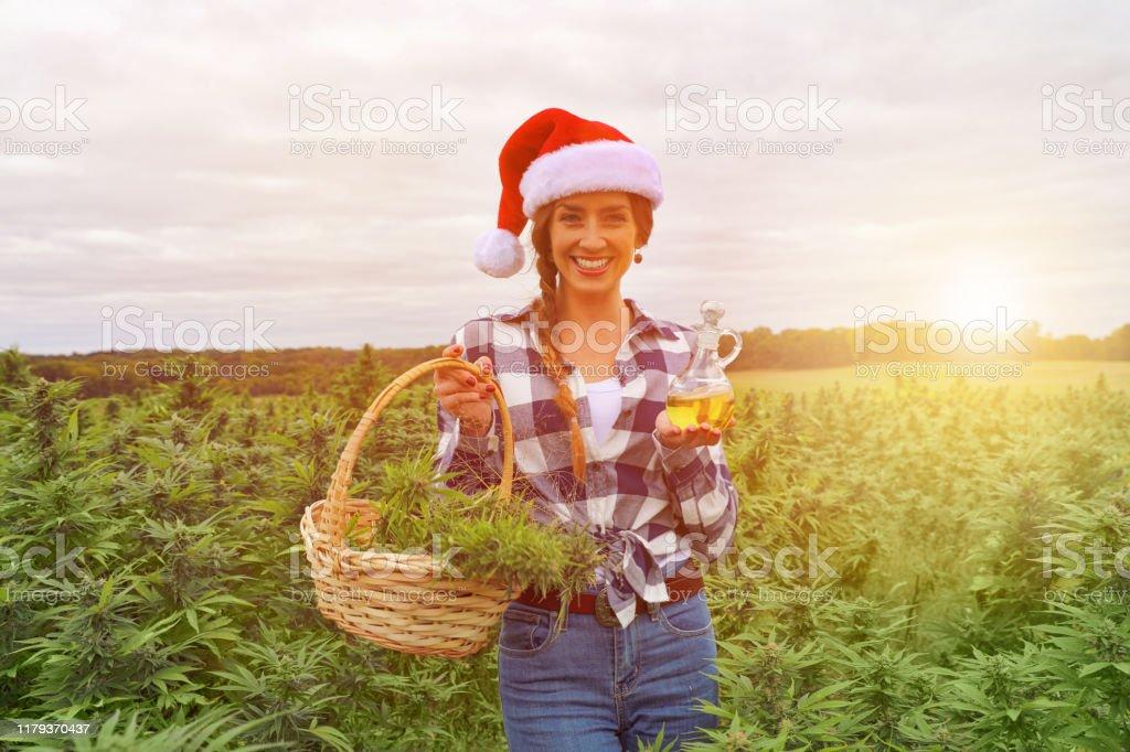 Junge Frau hält Korb mit Cannabisknospen und CBD-Öl - Lizenzfrei Weihnachten Stock-Foto