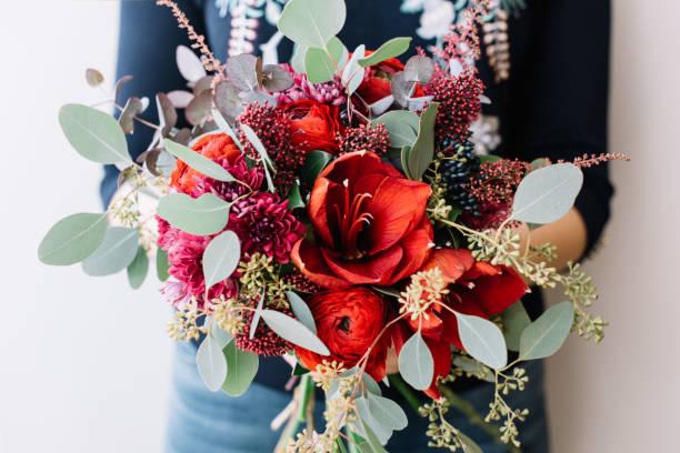 junge frau mit schönen frischen blühenden blumeblumenstrauß in roten farben - hipster braut stock-fotos und bilder