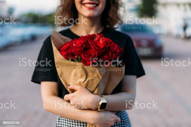 Young woman holding beautiful red flowers bouquet picture id995553192?b=1&k=6&m=995553192&s=612x612&h=sftpyoidnd3qyddlgllpytzrh8g65hq4 rbmremm30e=