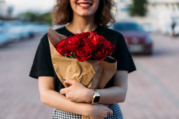 junge frau mit wunderschönen roten blüten bouquet - originelle geburtstagsgeschenke stock-fotos und bilder