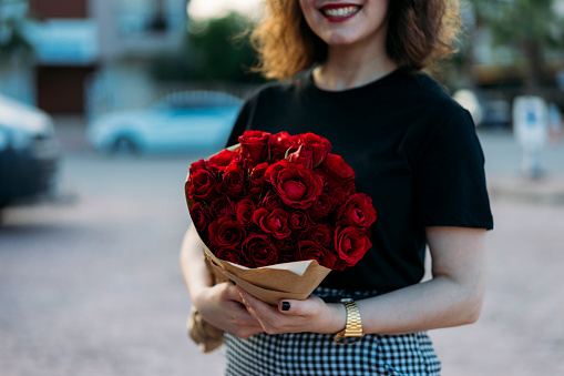Young woman holding beautiful red flowers bouquet