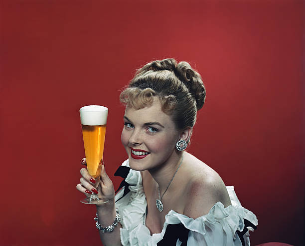 Young woman holding beer glass, smiling, portrait stock photo