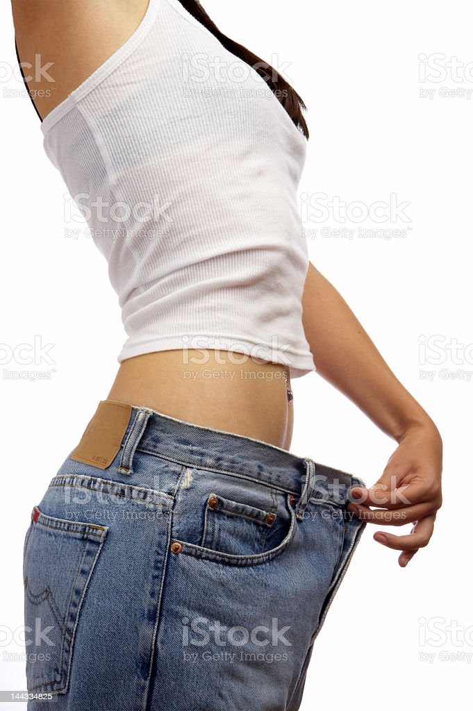 A young woman holding bigger fitted pants stock photo