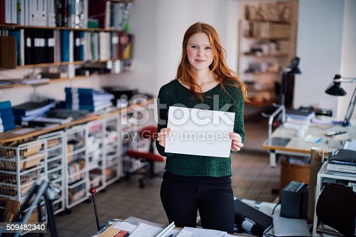 istock Young woman  holding blank board 509482340