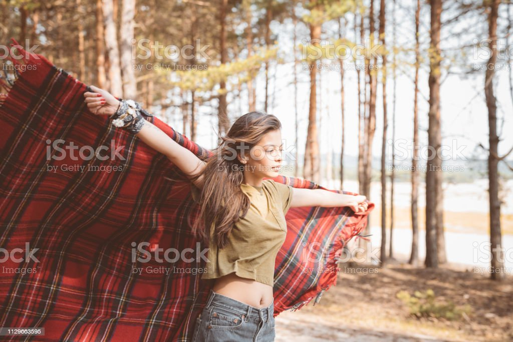 Young woman holding blanket with arms outstretched Beautiful brunette holding blanket with arms outstretched. Young woman is standing in forest. She is hiking during weekend. 25-29 Years Stock Photo