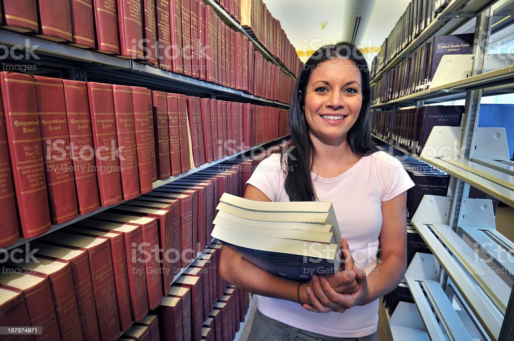 Young woman holding books at the library royalty-free stock photo