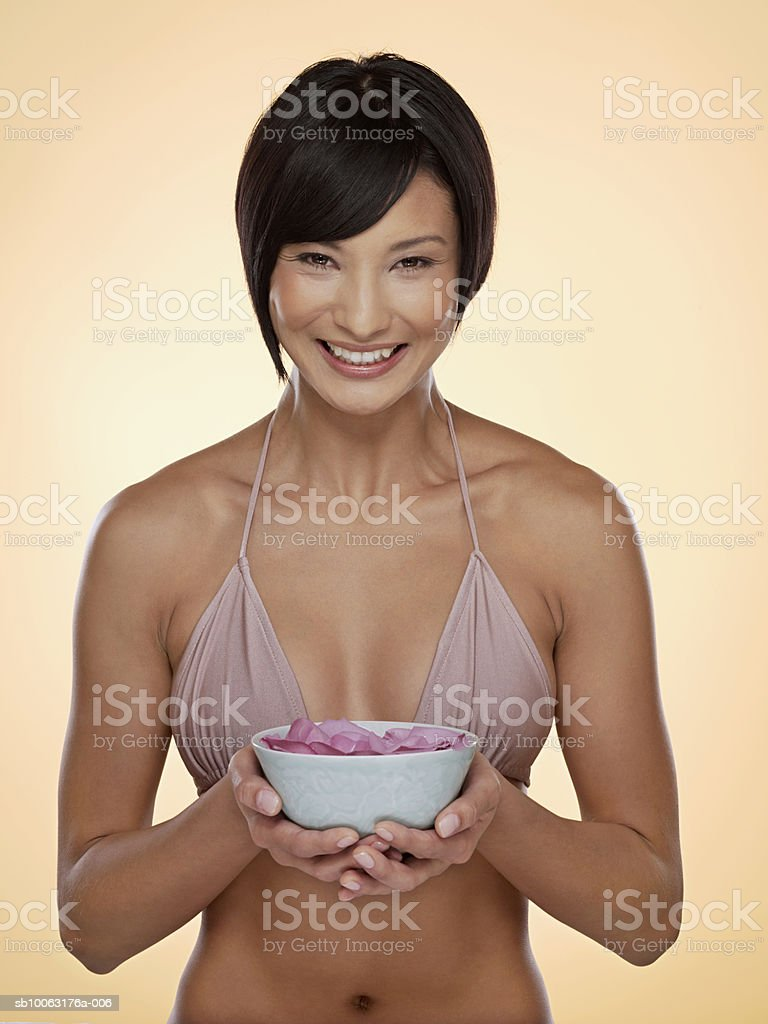 Young woman holding bowl of flowers, smiling, portrait photo libre de droits