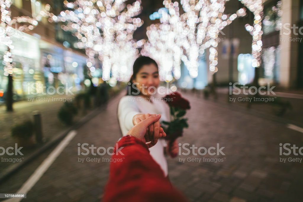 A young Japanese woman is holding her boyfriend's hand and leading...